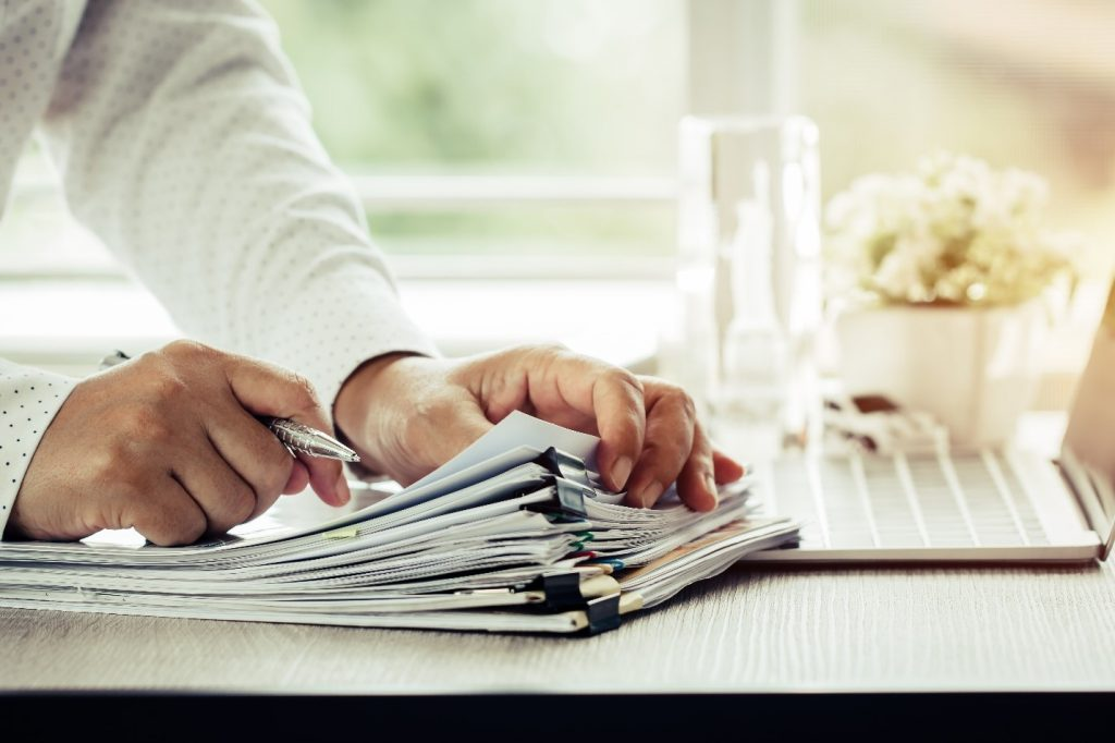 a person sifting through multiple paper checks