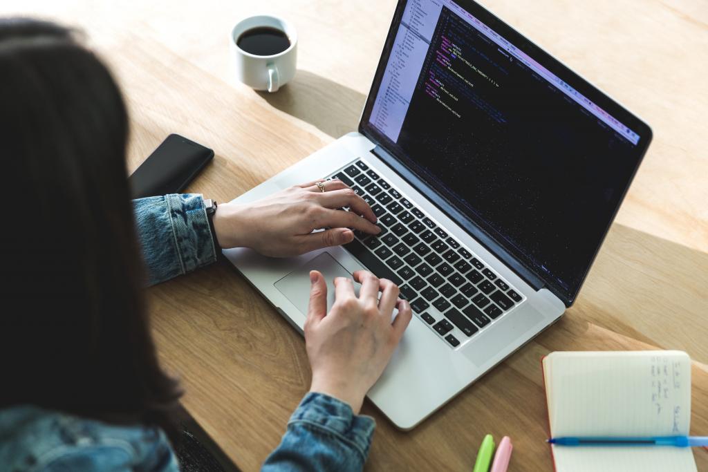 Women coding at a laptop